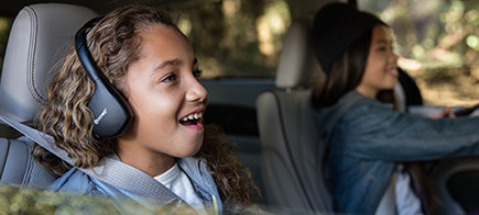 Child wearing noise cancelling headphones sitting in the second row seat of a vehicle.