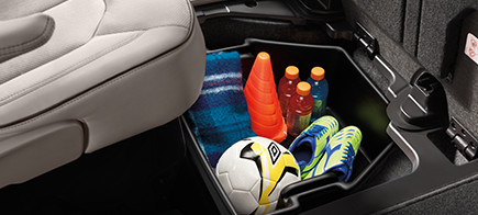 Soccer equipment including a soccer ball, soccer cleats, orange cones, and sports drinks stowed in the in-floor storage of a car.