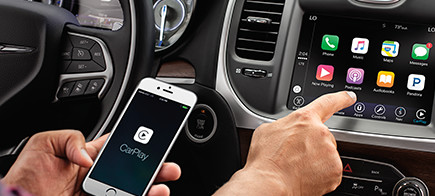 Man using Apple Carplay to connect his phone to his car.
