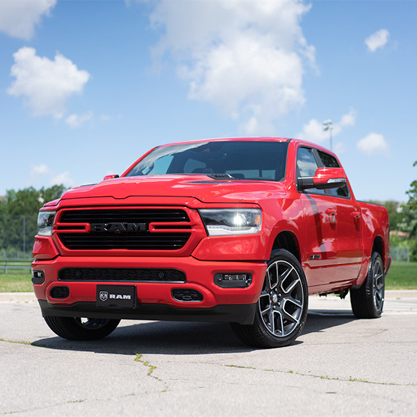 Front view of the red 2020 Ram 1500 Sport parked in an empty lot in front of a baseball field.