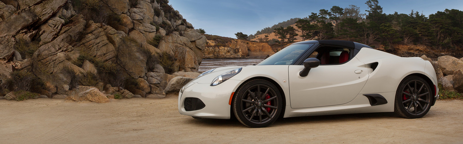 Side view of the white 2019 Alfa Romeo 4C Spider parked on a dirt-covered field besides rocks