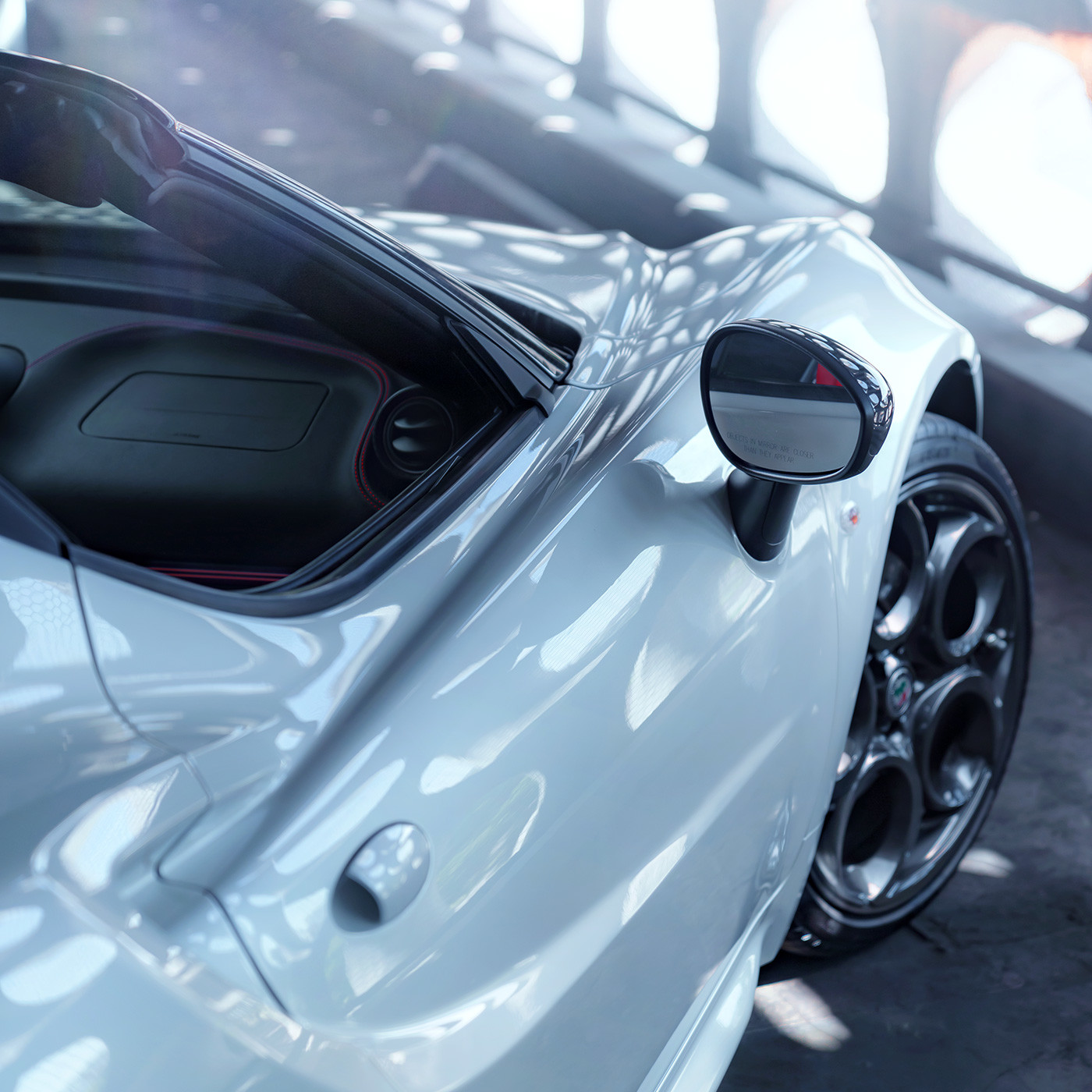 Alfa Romeo 4C spider side mirror and door shown with white exterior