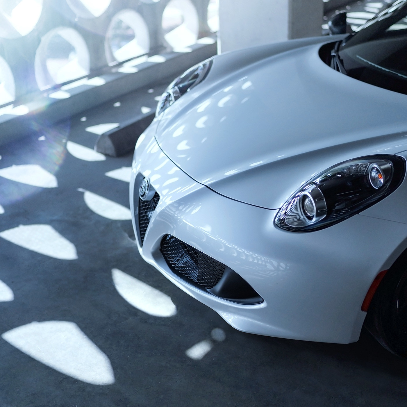 Front headlights and hood of white Alfa Romeo 4C spider