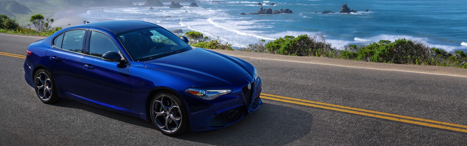 Blue 2019 Alfa Romeo Giulia being driven on a paved road along a coastline.
