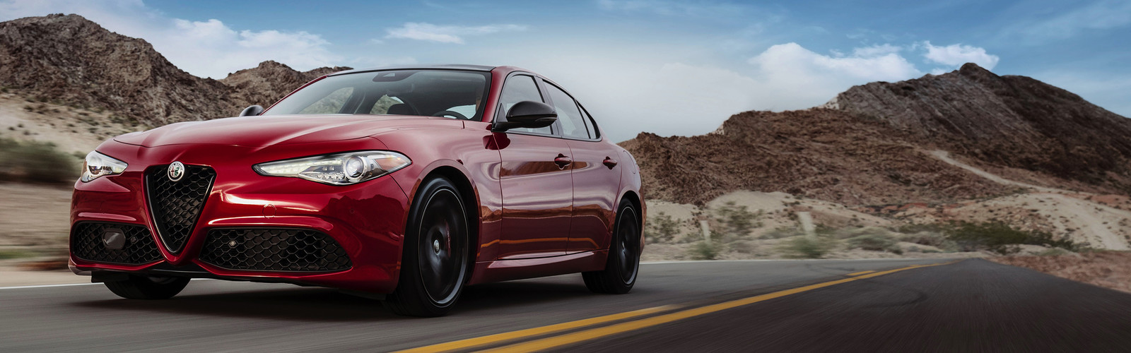 Front view of the red 2019 Alfa Romeo Giulia driving down a road in a desert
