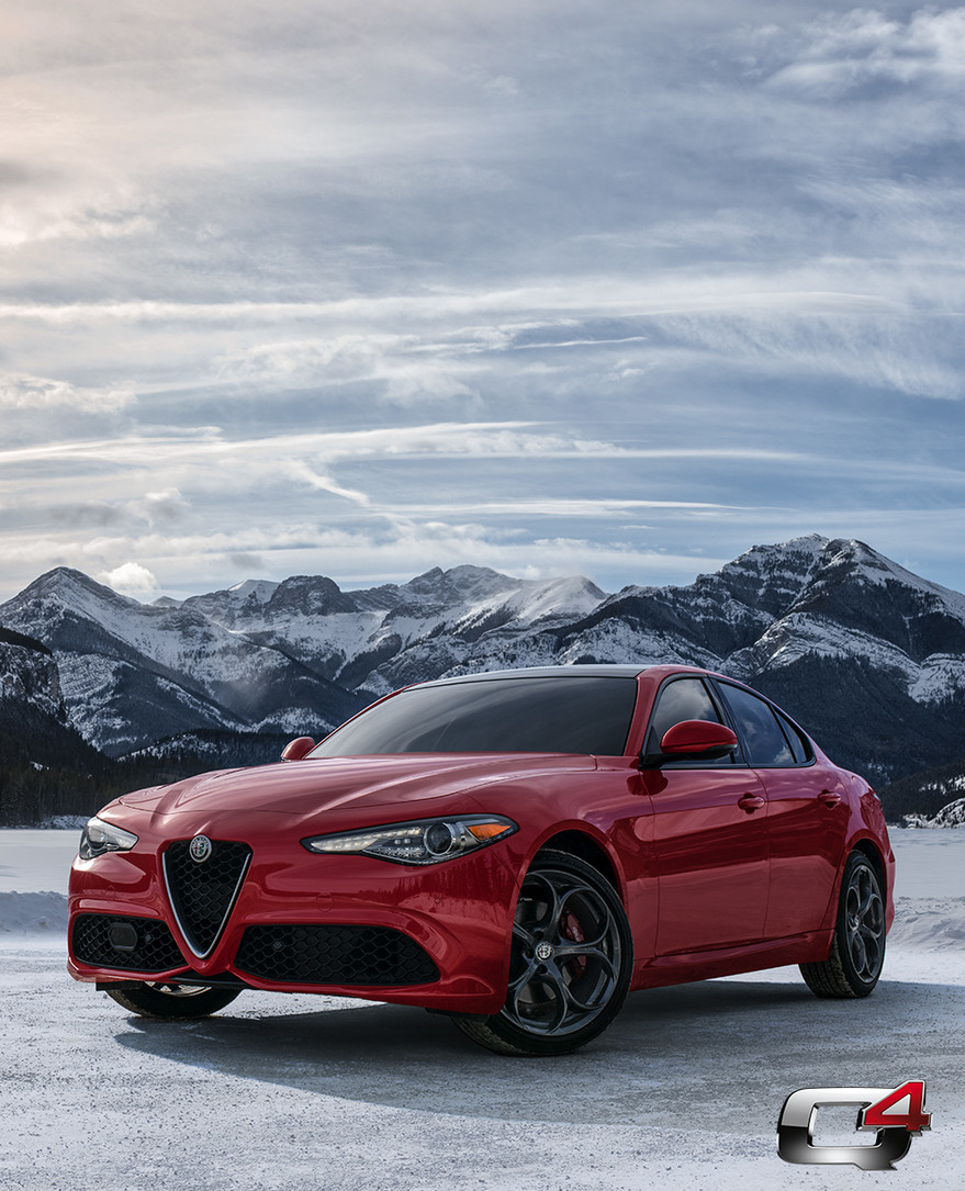 Front view of the red 2019 Alfa Romeo Giulia parked on a snow-covered field in the mountains