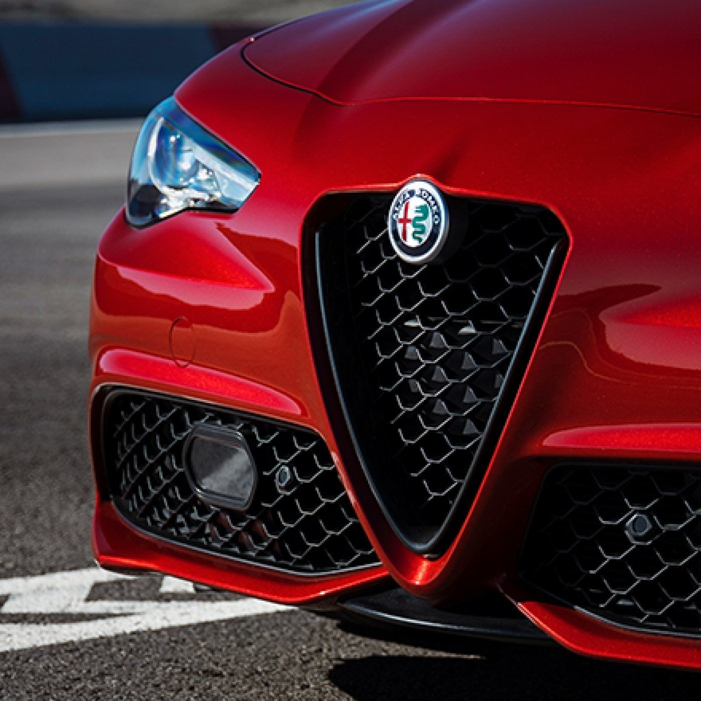 Front view of the red 2019 Alfa Romeo Giulia showing its Bi-Xenon headlights and the Scudetto grille