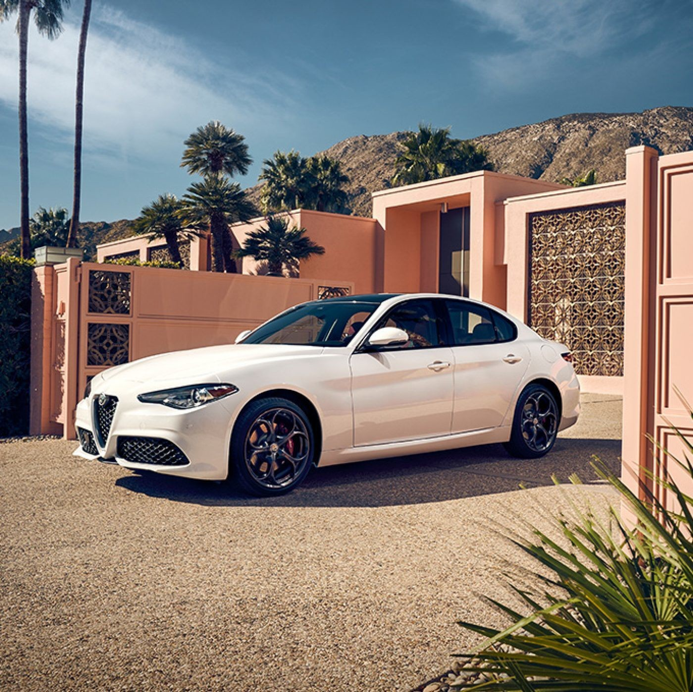 Side view of the white 2019 Alfa Romeo Giulia pulling out of a driveway