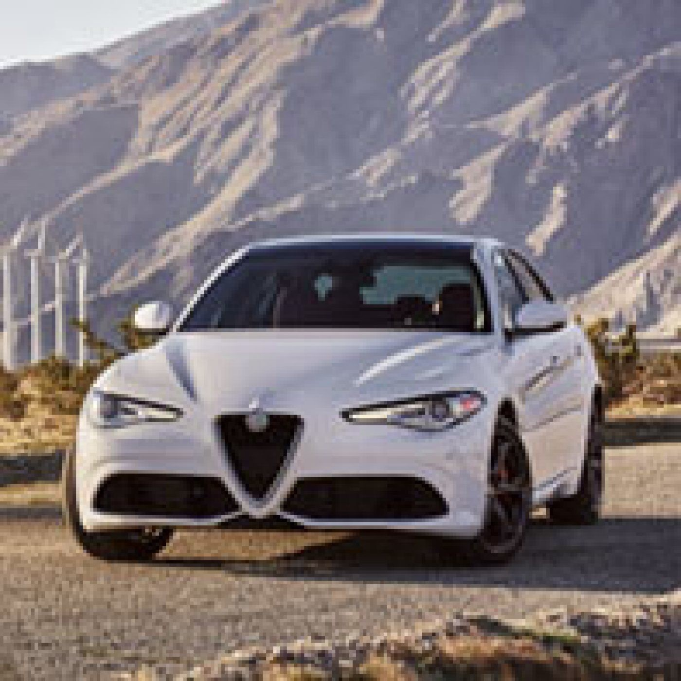 Front view of the white 2019 Alfa Romeo Giulia parked on a street in front of a mountain