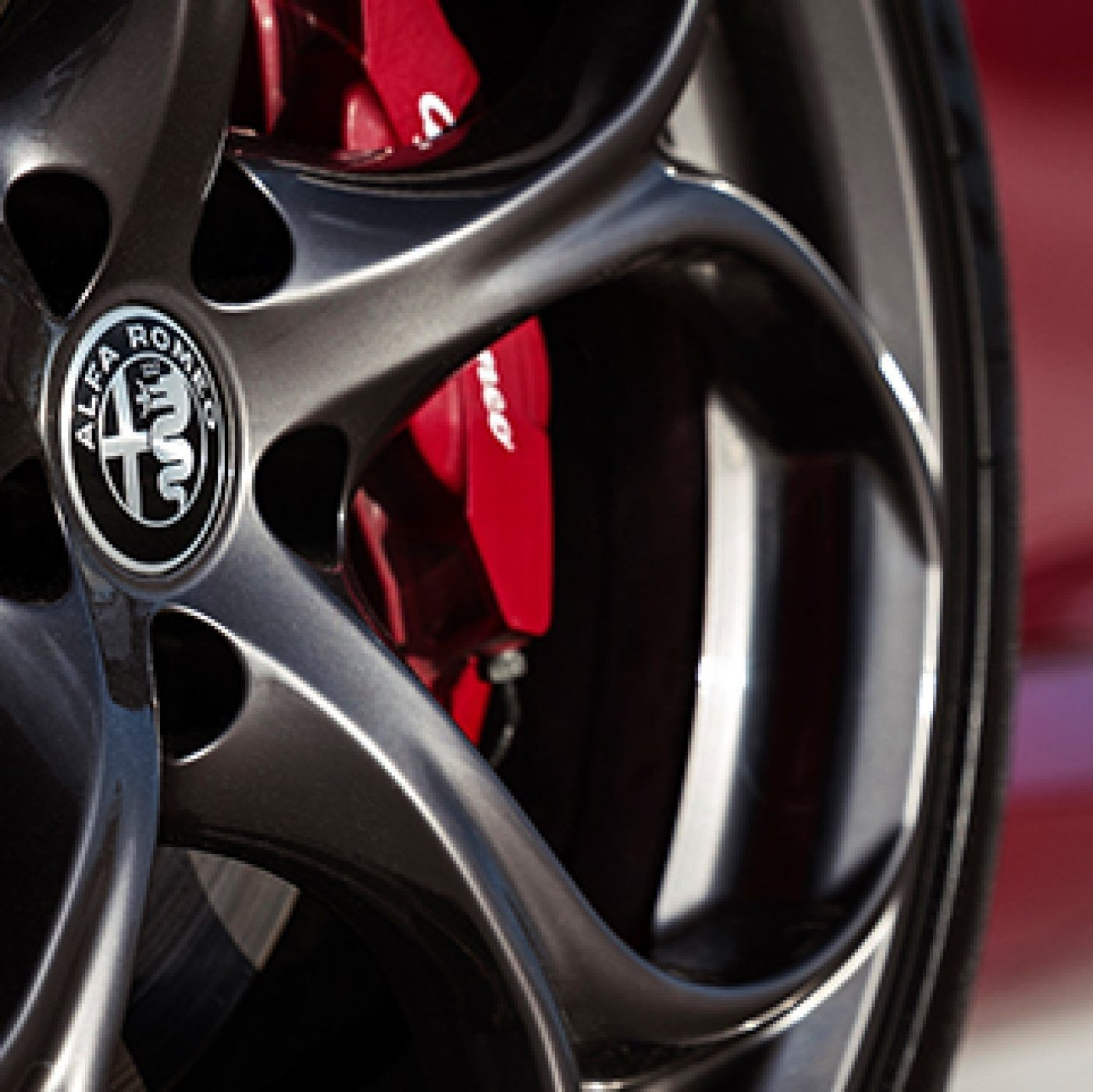 The Y-spoke aluminum wheels of the red 2019 Alfa Romeo Giulia