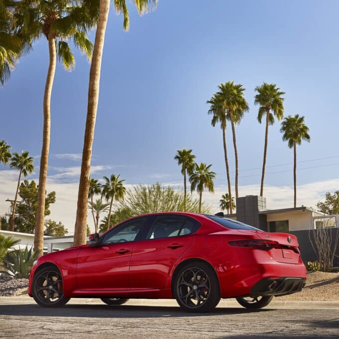 The 2020 Alfa Romeo Giulia parked outside a home in a desert setting.