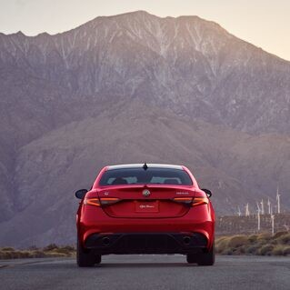 A rear view of the 2020 Alfa Romeo Giulia being driven toward a wind farm in the mountains.