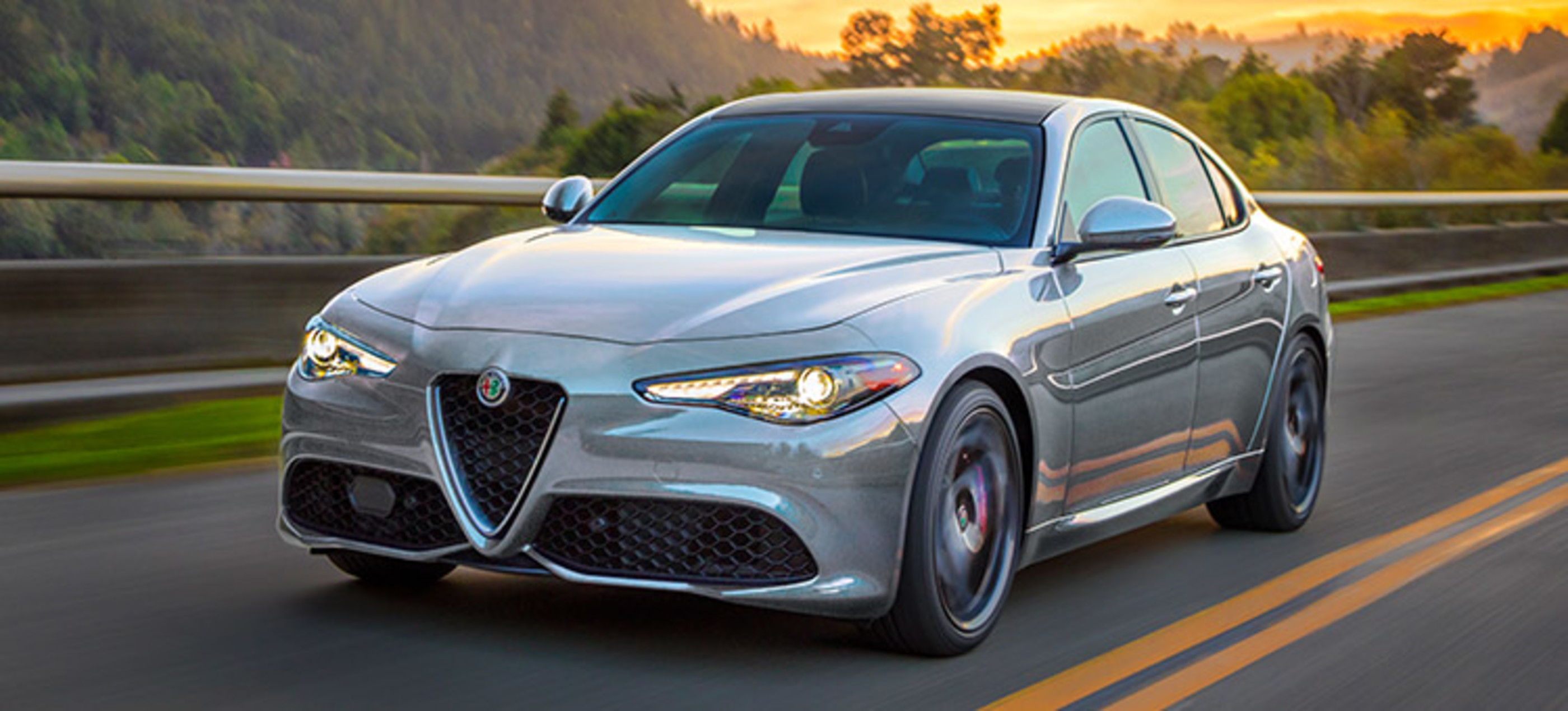 Front view of a silver Alfa Romeo Giulia, being driven on road in the mountains