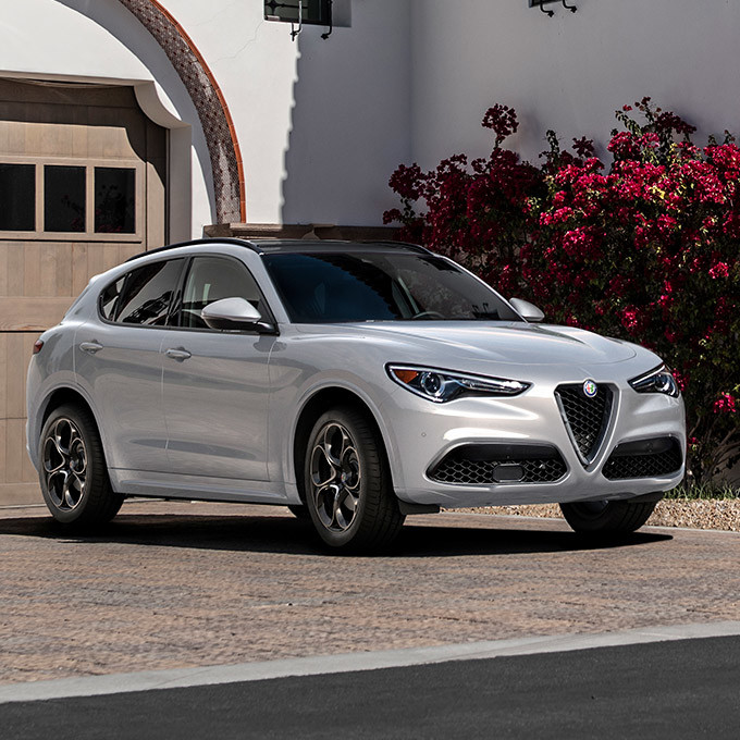 A front view of an Alfa White 2021 Alfa Romeo Stelvio parked in front of the garage of an Italian villa.