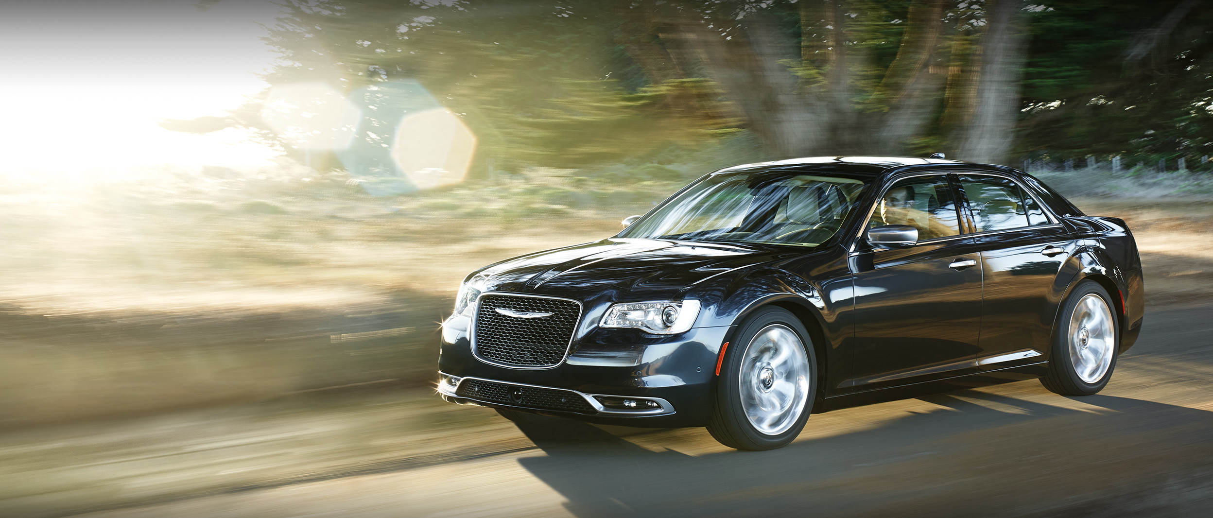 Black Chrysler 300 Speeding Down a Forest Trail