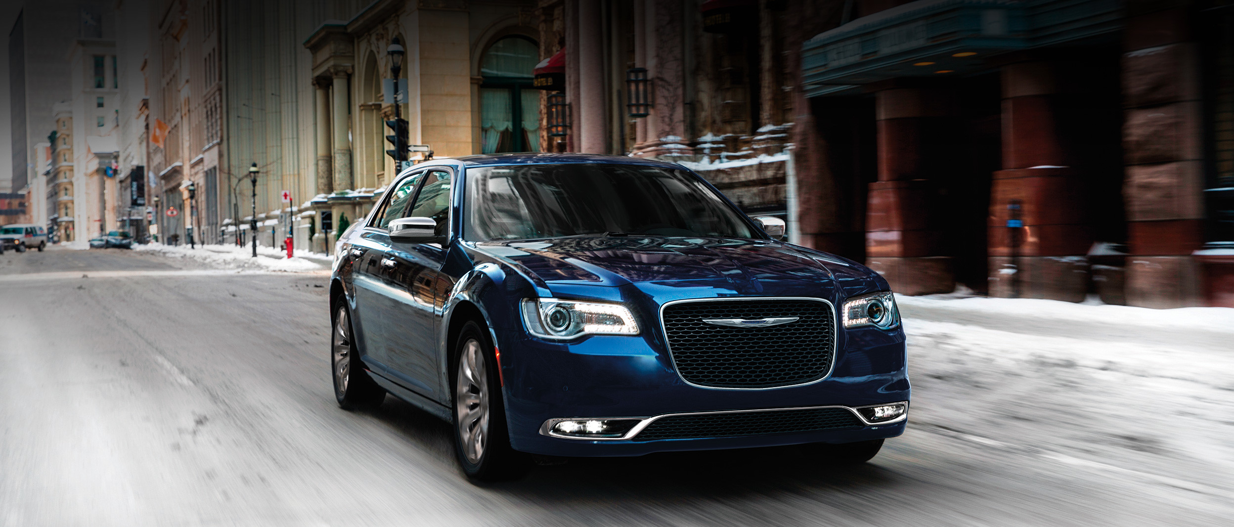 The blue 2020 Chrysler 300 being driven on a road in urban area