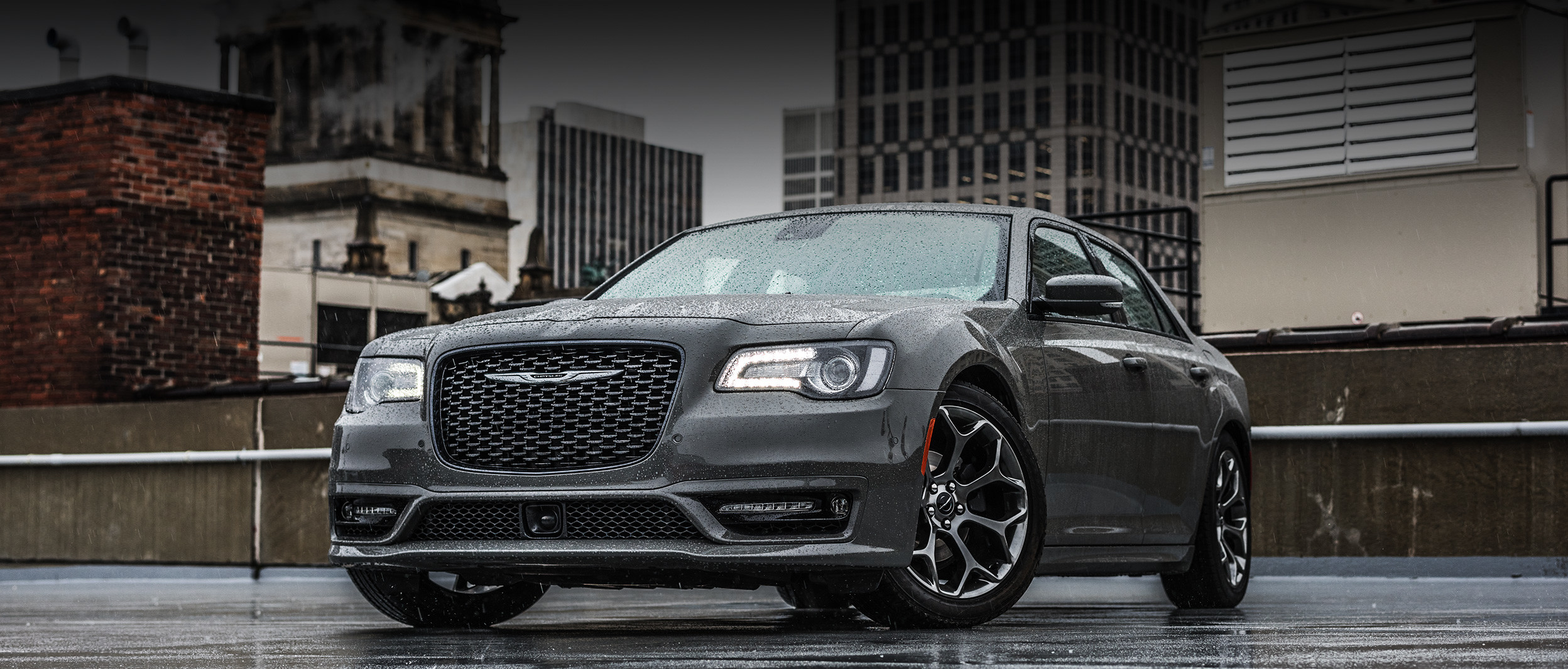 Grey 2020 Chrysler 300, parked outside in a city in the rain.