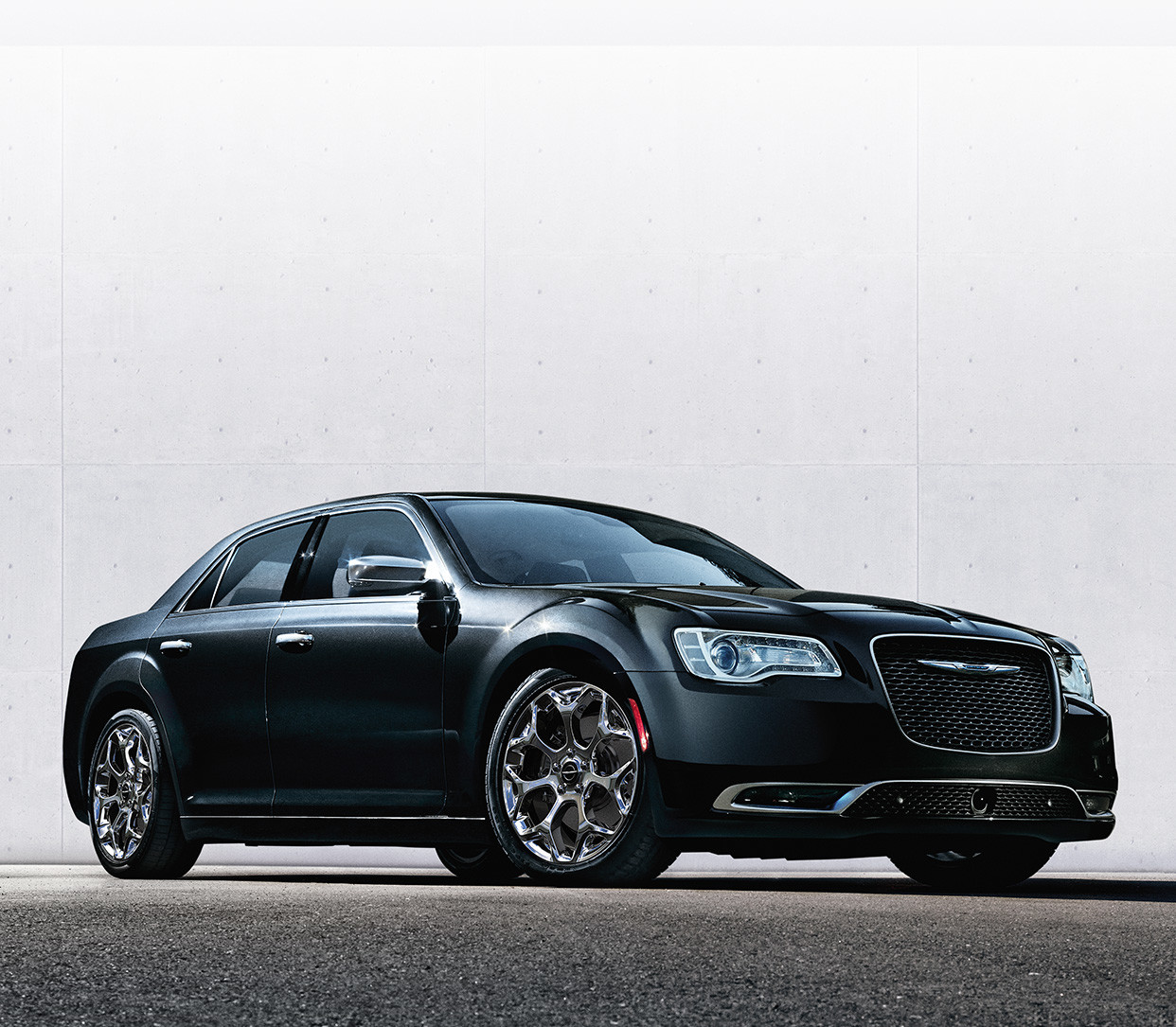 Side view of the black 2020 Chrysler 300 parked on a road in front of white wall