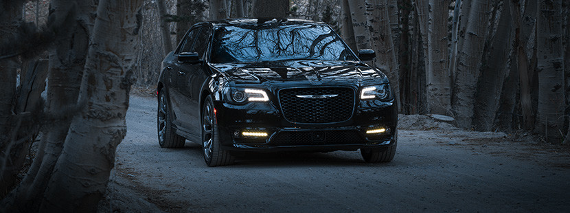The black 2020 Chrysler 300 driving through trees on a gravel road in a forest at night