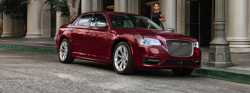 Woman wearing a black dress getting into the driver's seat of a red 2020 Chrysler 300, parked in front of a building.