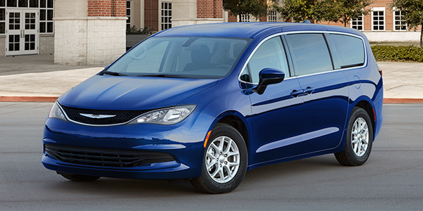 The new 2021 Chrysler Grand Caravan in dark blue parked in front of a building.