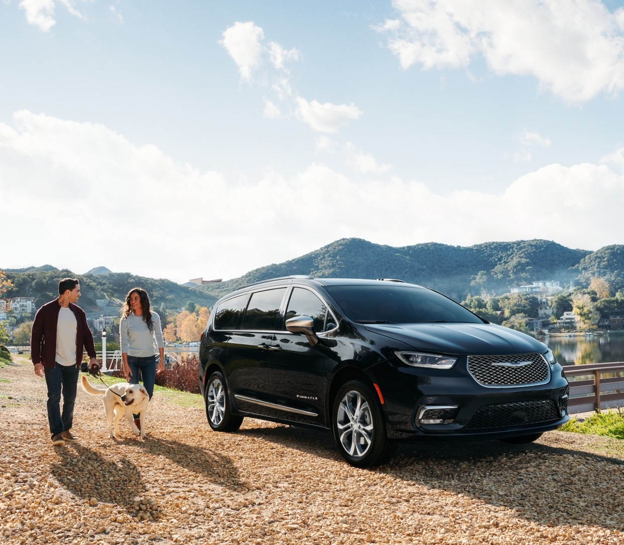 The new 2021 Chrysler Pacifica parked near a lake with mountains behind