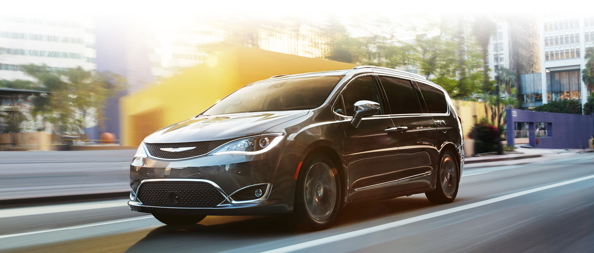 Grey Chrysler Pacifica Driving Through the City