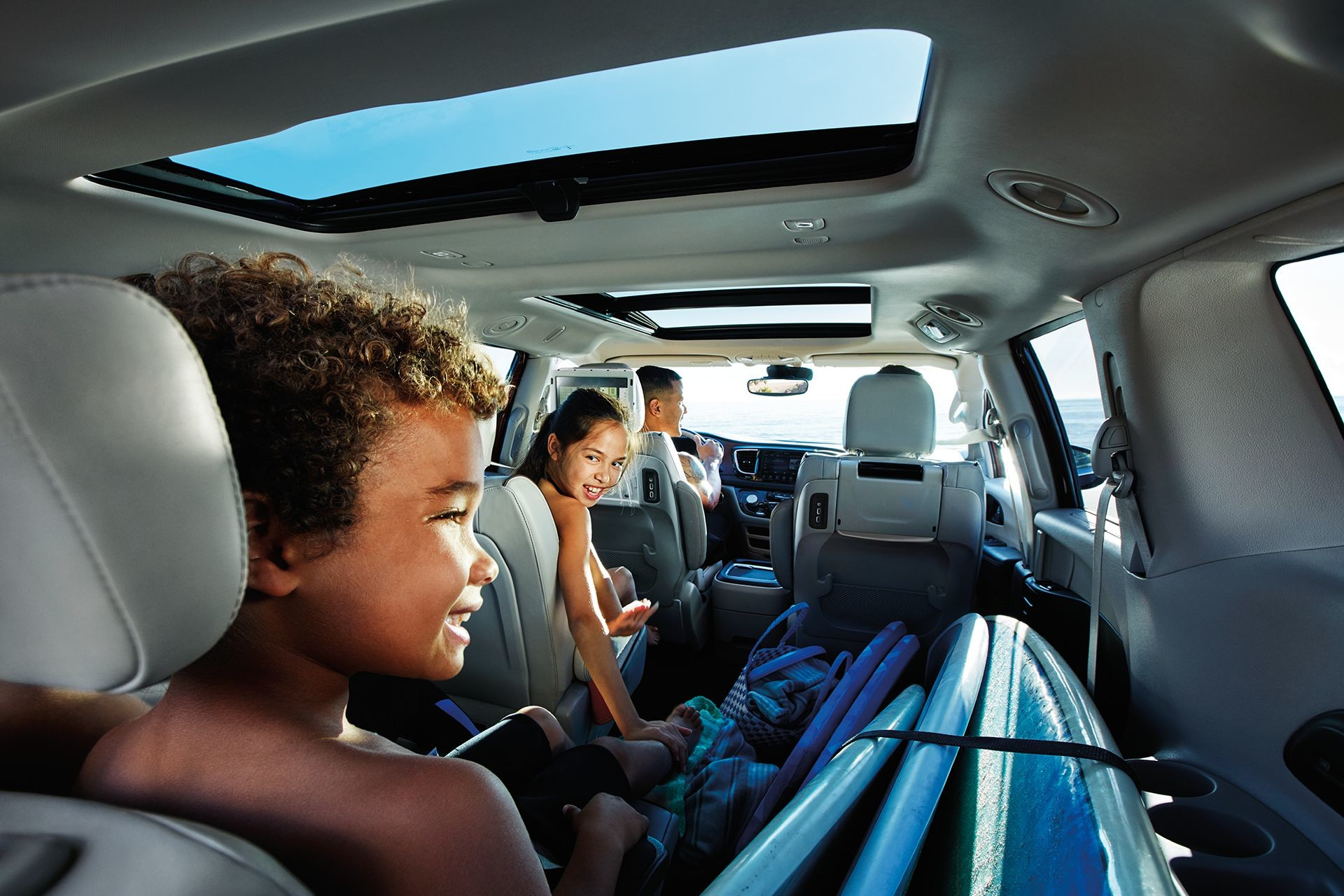 2019 Chrysler Pacifica surfboard placed next to 2 children