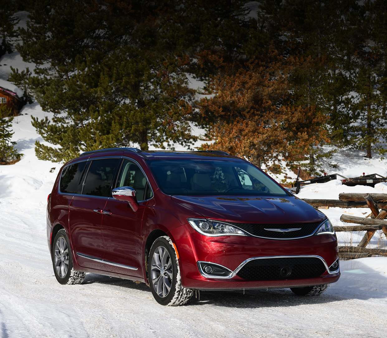 Front view of the red 2020 Chrysler Pacifica parked in a snowy forest next to a ski chalet