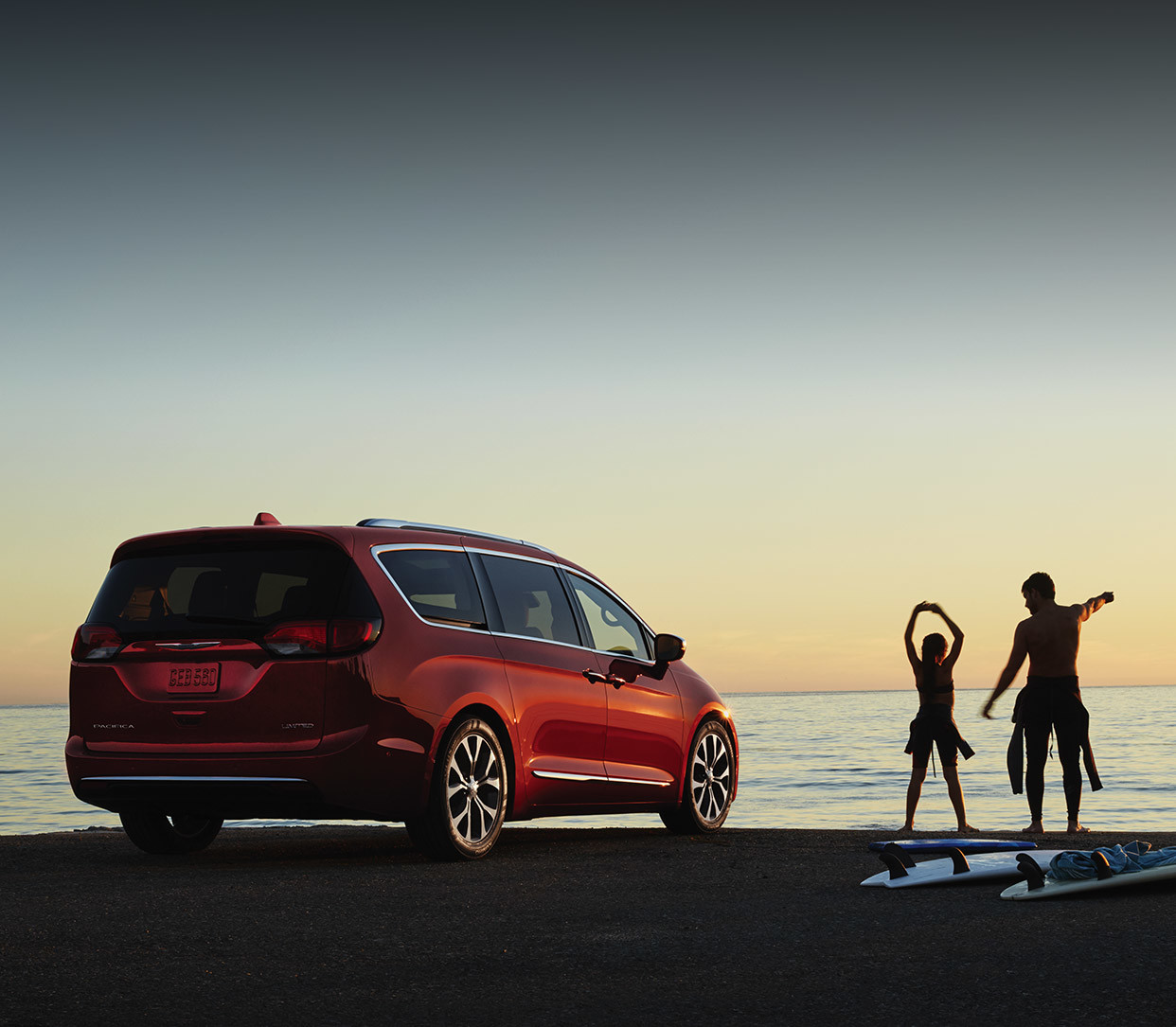 Dad and daughter with surfboards stretching next to a red 2020 Chrysler Pacifica.
