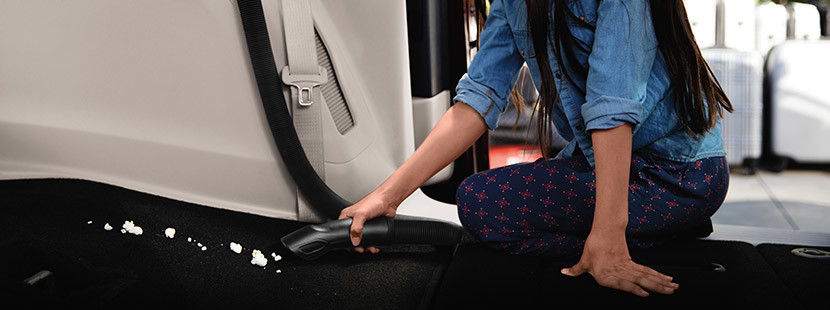 A woman cleaning the  floor of the 2020 Chrysler Pacifica using the built-in vacuum system