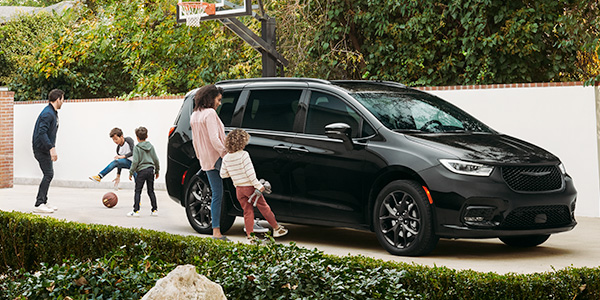 Black Chrysler Pacifica, parked on a driveway while a mother and daughter use the hands-free feature to open the side doors.