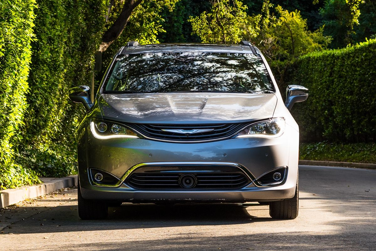 2019 Chrysler Pacifica Hybrid with silver exterior driving in the city.