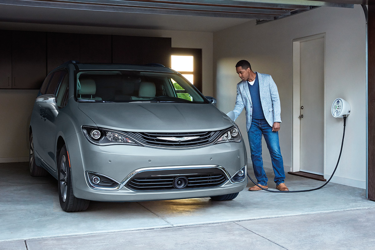 19MY Chrysler Pacifica Hybrid man charging minivan in garage