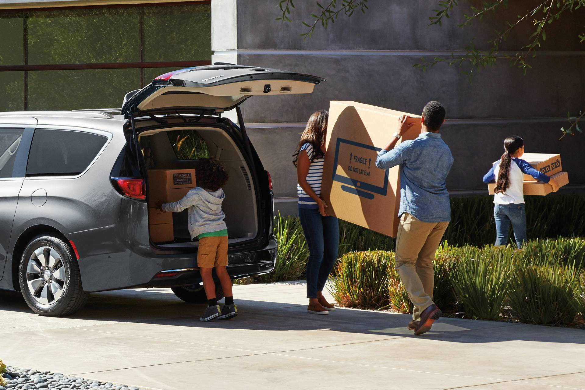 2019 Chrysler Pacifica Hybrid exterior shot of family unloading goods from trunk