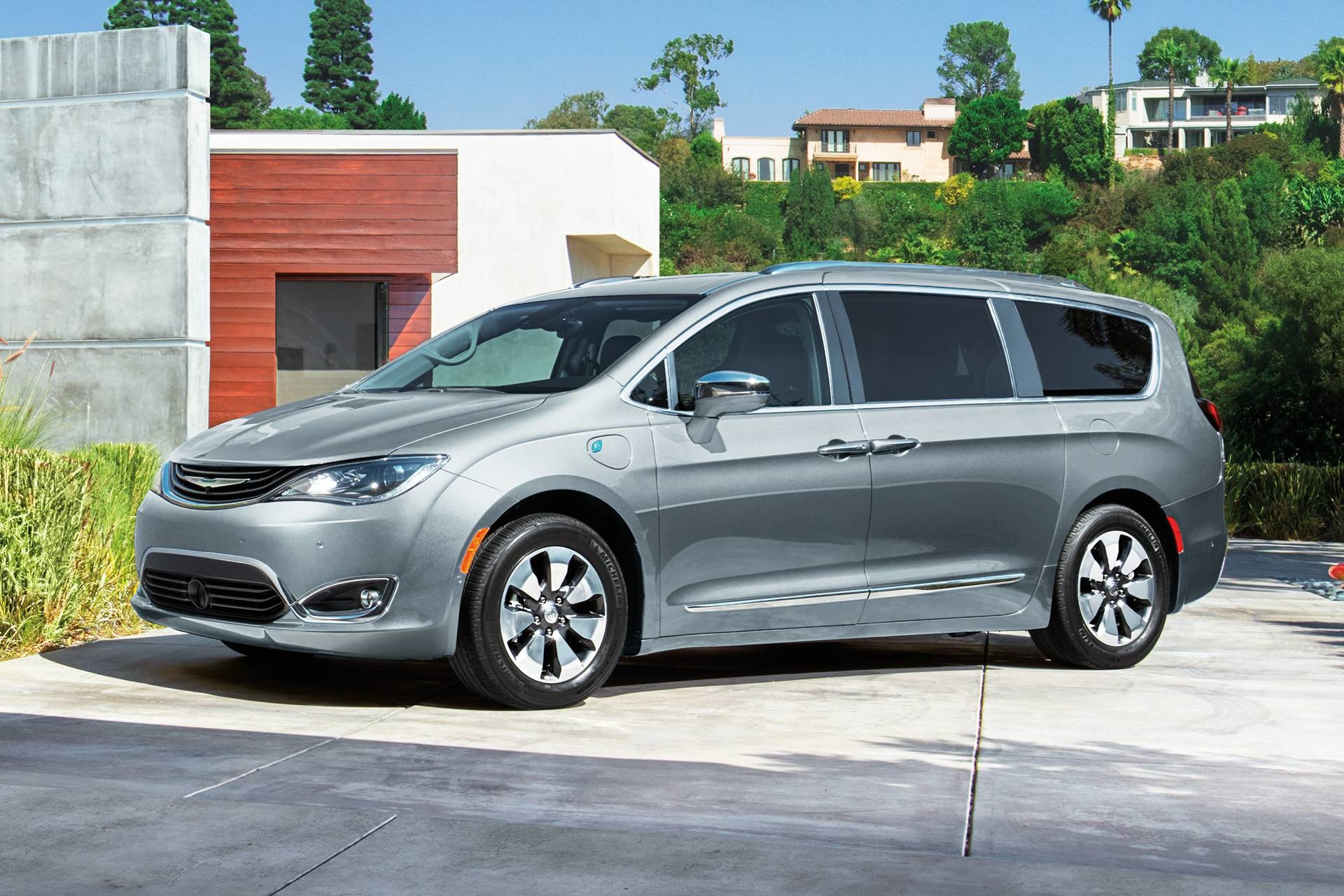 2019 Chrysler Pacifica Hybrid exterior shot of a Hybrid charging at a home, shown in silver