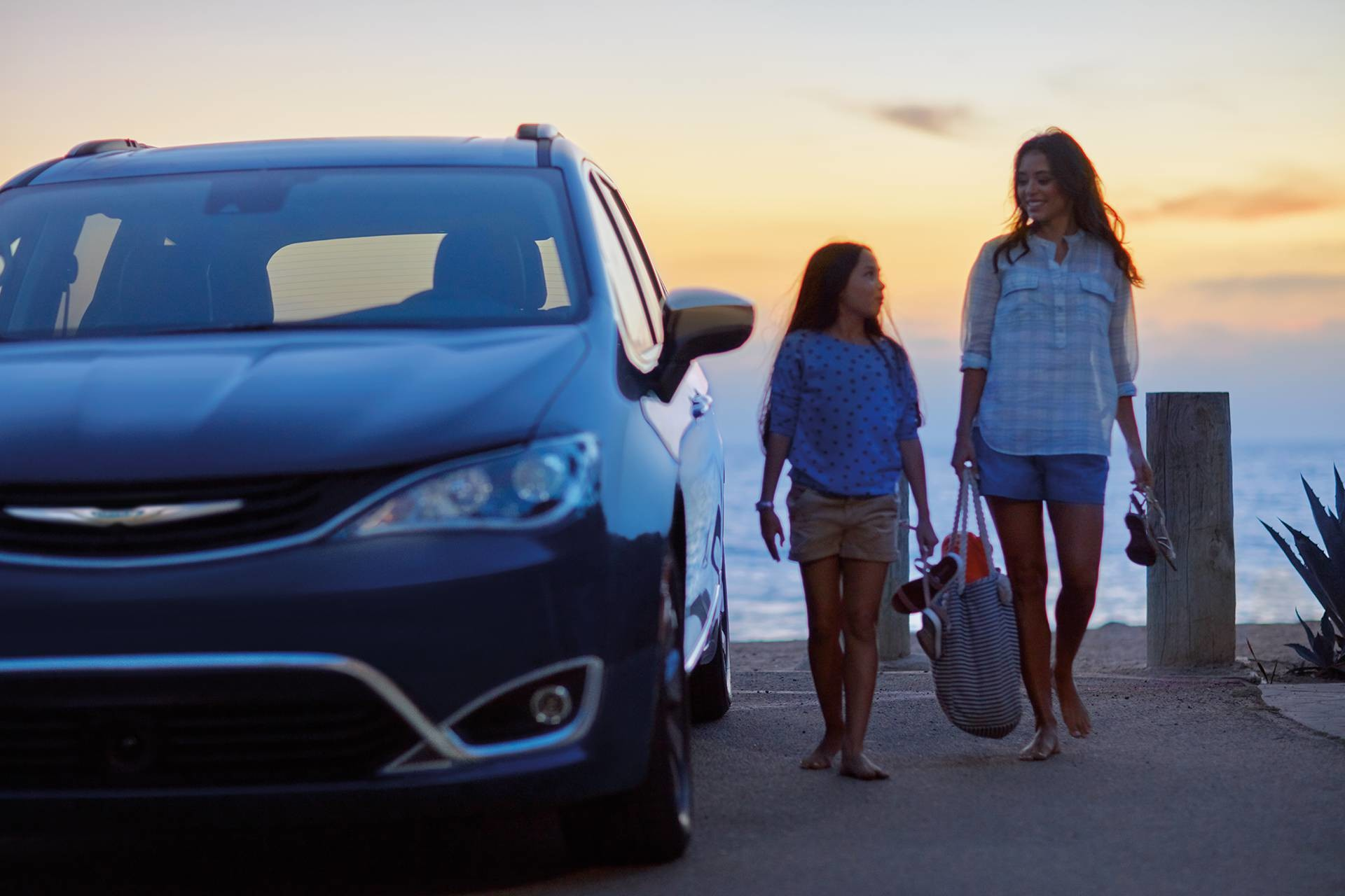 2019 Chrysler Pacifica Hybrid exterior front view with family next to car