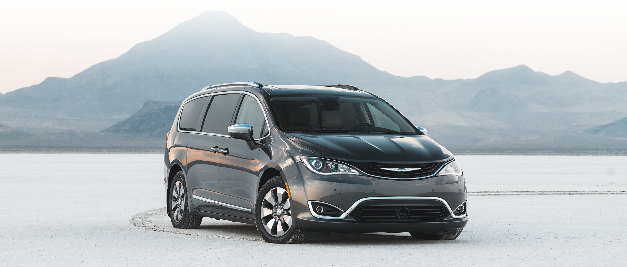 Front view of the grey 2019 Chrysler Pacifica Hybrid parked in a snowy mountain clearing