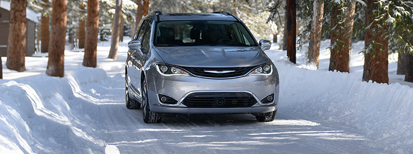 Front view of the silver 2019 Chrysler Pacifica Hybrid driving on a snow-covered road in the forest