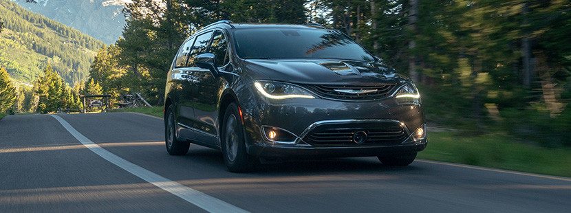 Grey 2019 Chrysler Pacifica Hybrid being driven on a paved road through a forest and mountains.