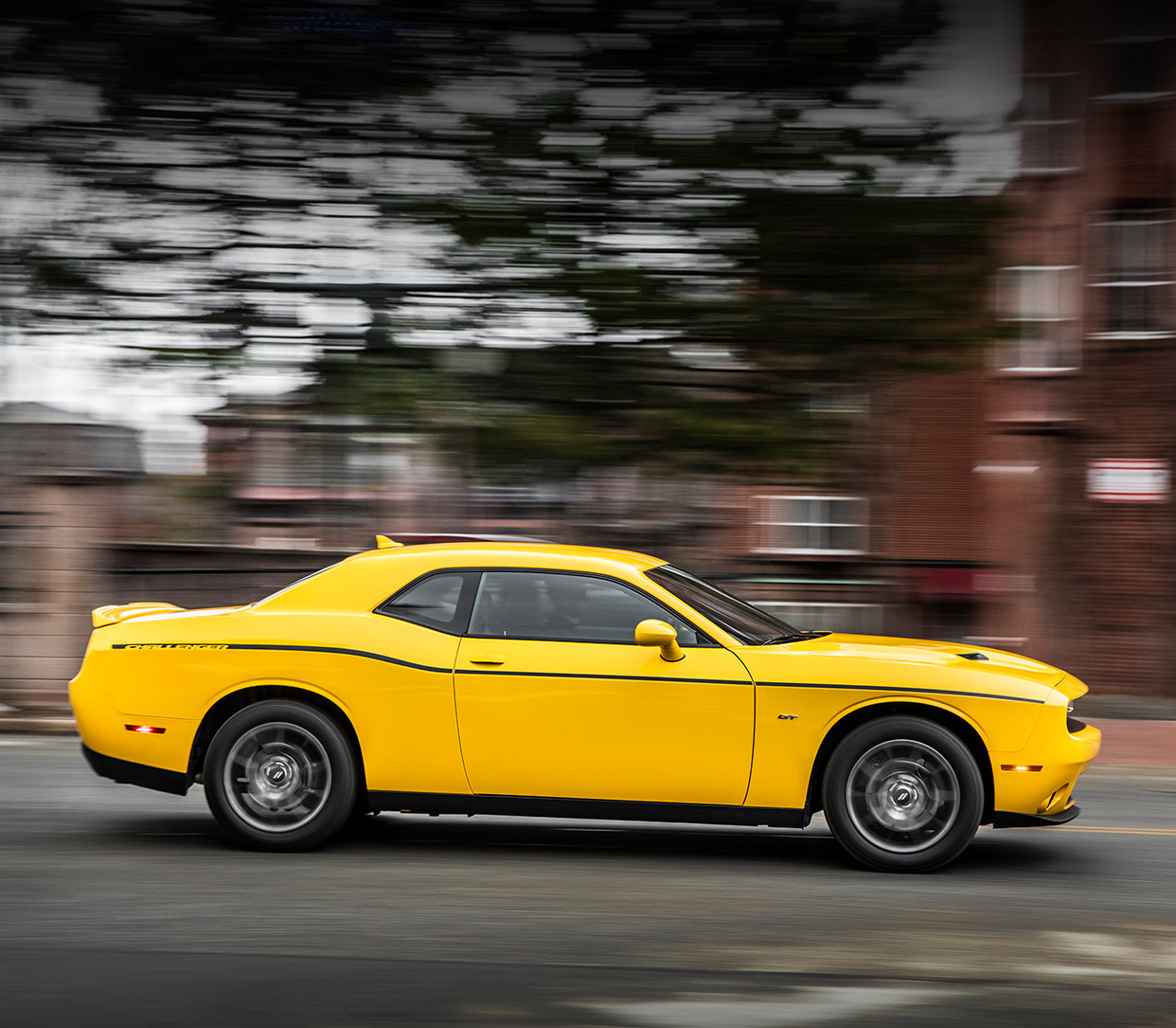 Yellow Dodge Challenger Driving Down a Street
