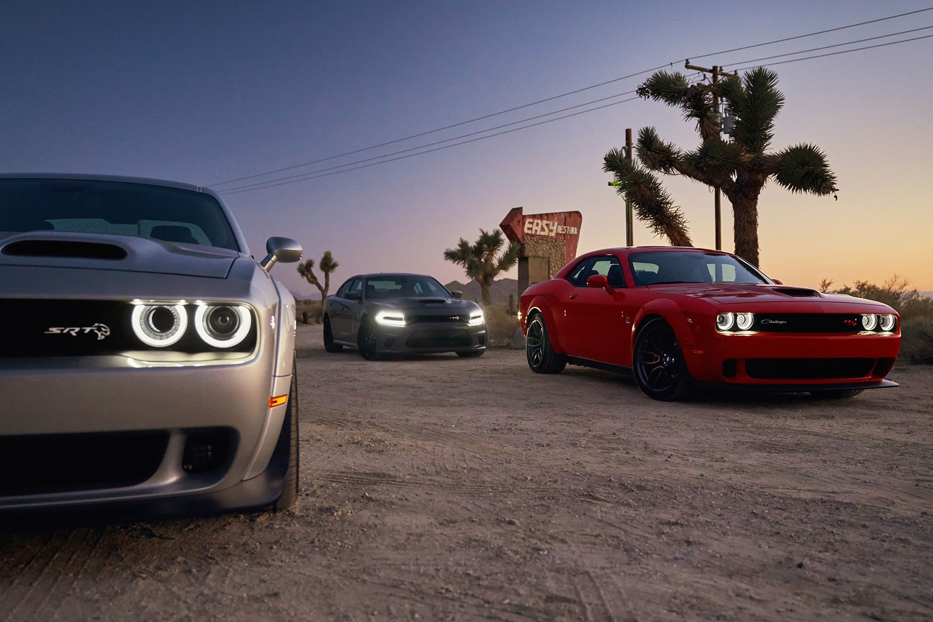 Two 2019 Dodge Challengers and one 2019 Dodge Charger parked in the desert