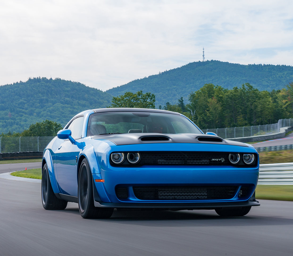 Blue Dodge Challenger Speeding Around a Racetrack