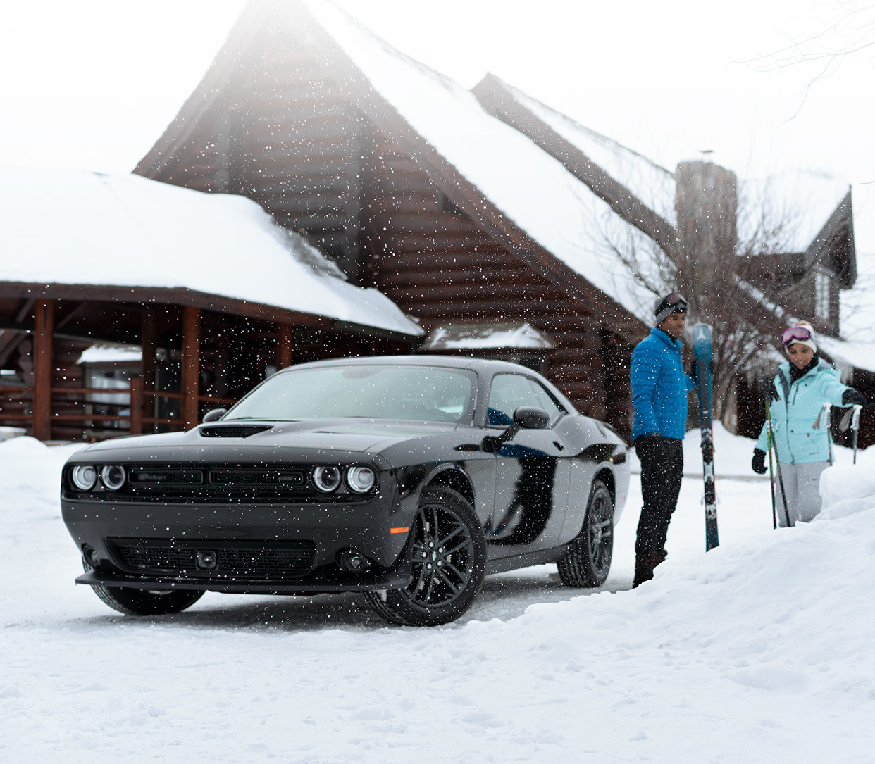 Front view of the black 2019 Dodge Challenger parked in the snow outside of a mountain cabin