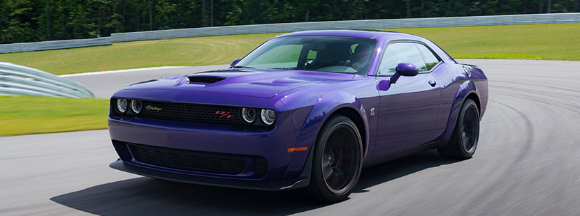 Purple Dodge Challenger Driving Around a Curve