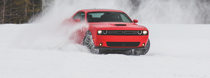 Front view of the red 2019 Dodge Challenger driving through the snow on a mountain