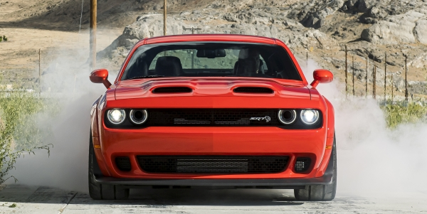 Front view of a Red 2021 Dodge Challenger driving through a dirt road.
