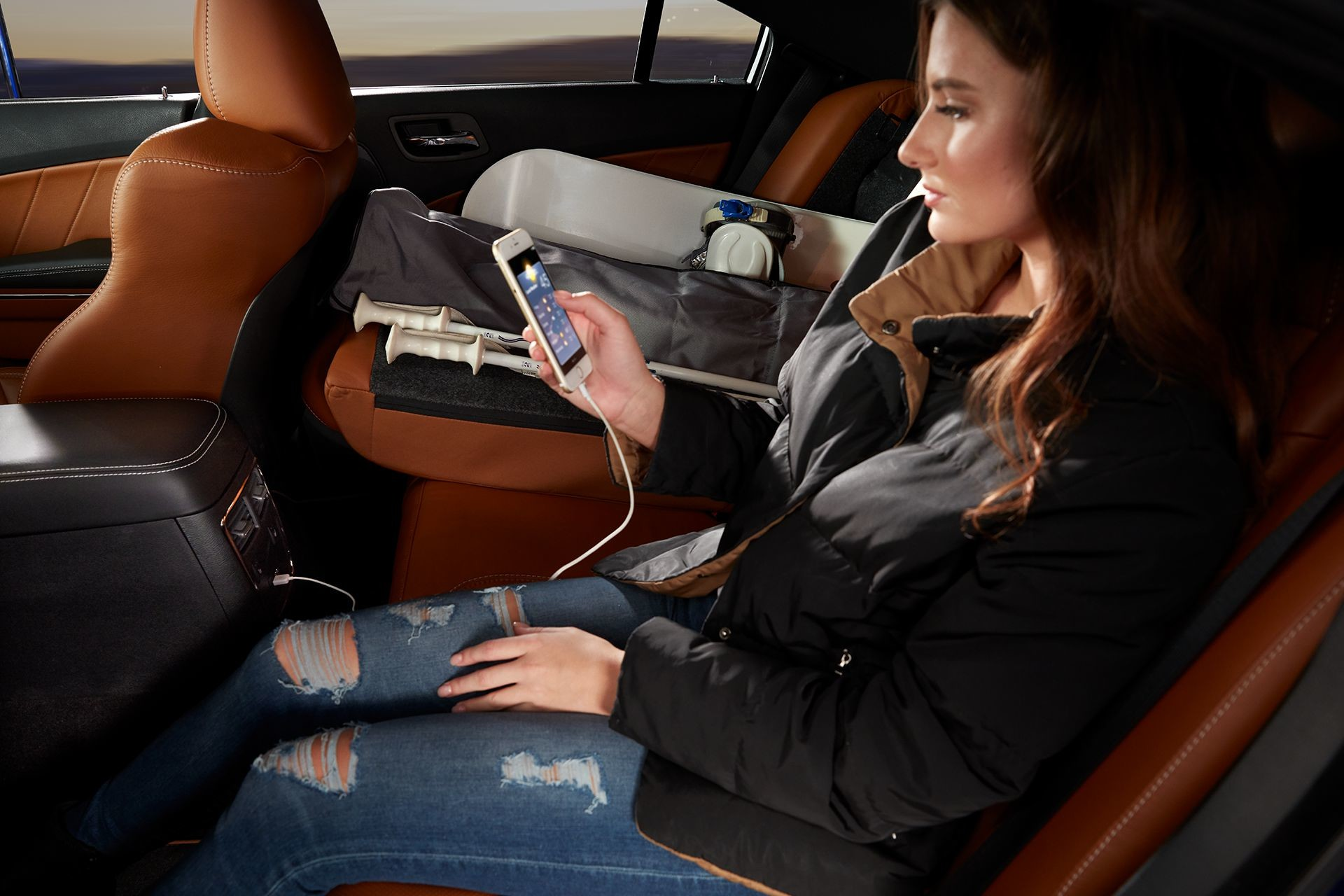2019 Dodge Charger comfortable rear seats with a woman holding a smartphone