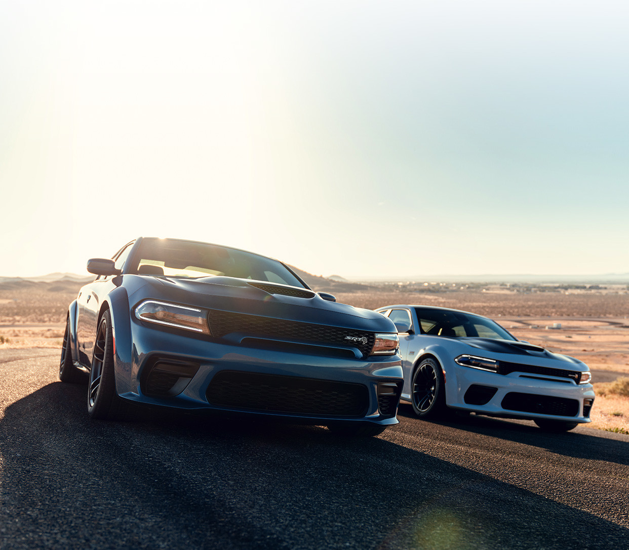 The blue 2020 Dodge Charger being driven on a road in a desert beside the white 2020 Dodge Charger