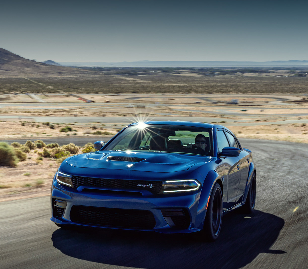 The blue 2020 Dodge Charger driving through plains on the road in a desert